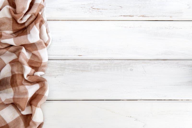 A toalha de mesa ou o guardanapo quadriculado marrom amarrotado na tabela de madeira branca vazia com espaço da cópia para o alim fotografia de stock royalty free