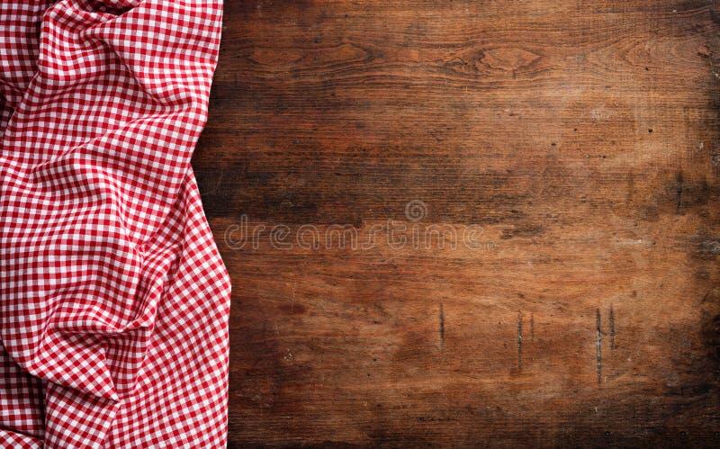 Toalha de mesa quadriculado branca vermelha do piquenique no fundo de madeira, espaço da cópia imagens de stock