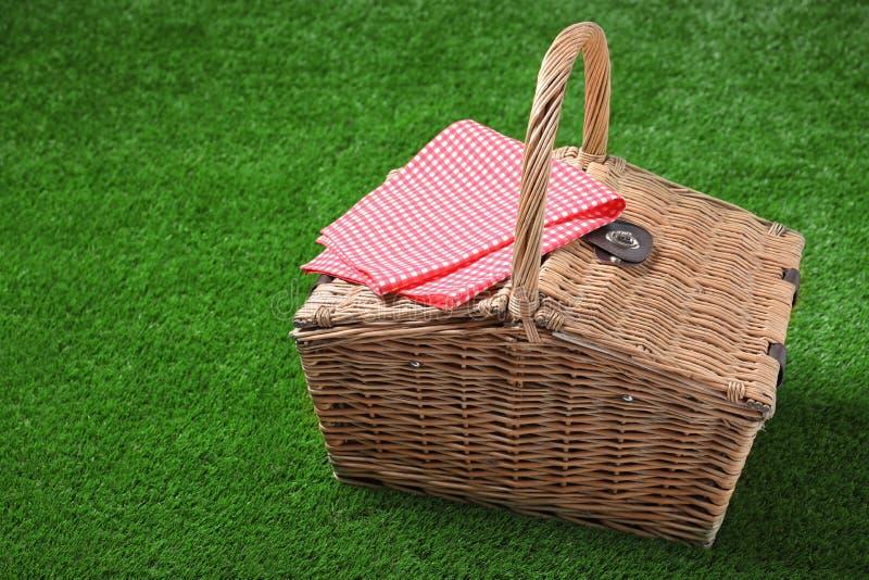 Toalha de mesa quadriculado e cesta de vime fechado do piquenique na grama verde foto de stock royalty free