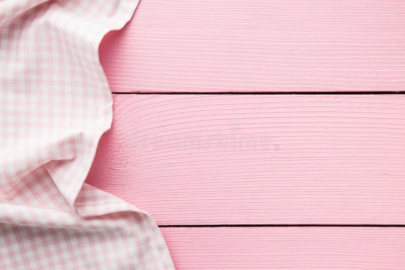 Toalha de mesa quadriculado sobre a tabela de madeira cor-de-rosa foto de stock