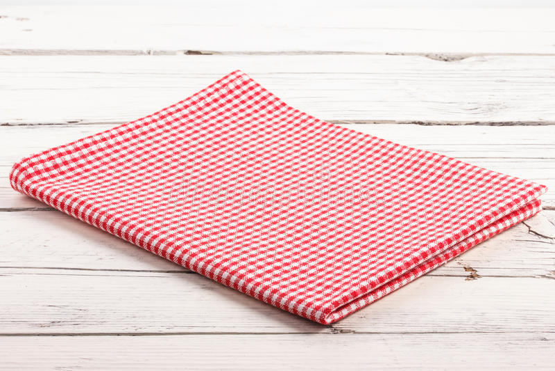 Toalha de mesa quadriculado vermelha dobrada na placa de madeira branca fotos de stock