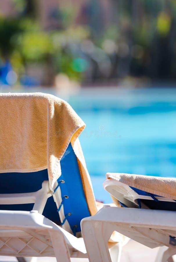 A toalha de praia na cor de creme pendurou na cadeira de plataforma vazia pelo s imagem de stock