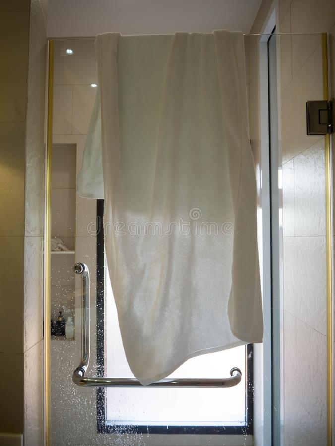 A toalha foi pendurada na porta de vidro no chuveiro fotografia de stock