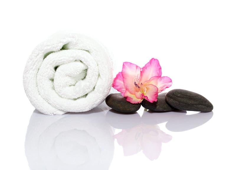 Toalha, gladiola e seixos para a massagem foto de stock royalty free