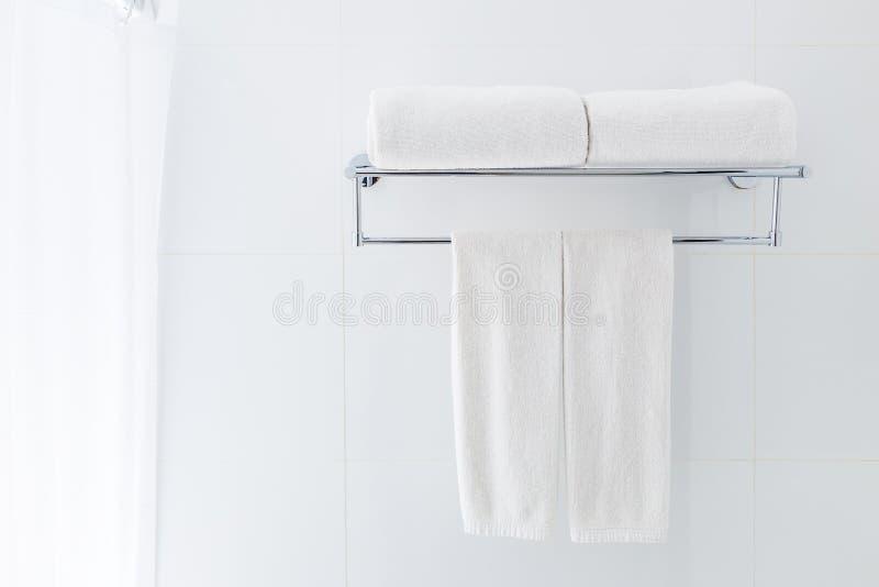 Toalhas brancas do banheiro que penduram na cremalheira em um ne branco do banheiro fotografia de stock