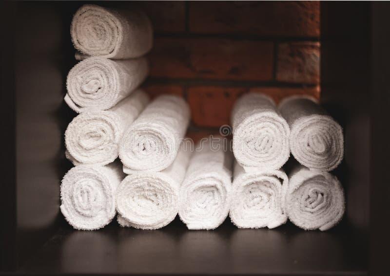 Toalhas brancas dobradas em um rolo Tijolo ao fundo Apresentação de têxteis Utilização racional do espaço imagem de stock royalty free
