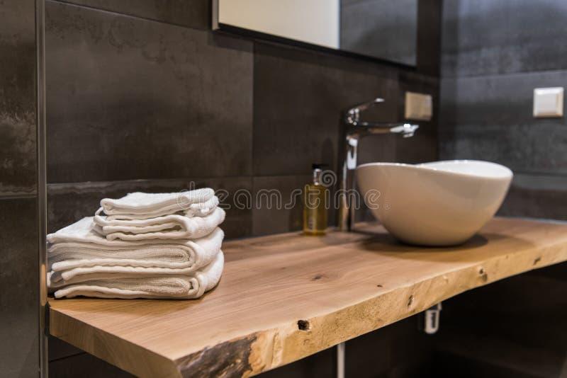 Toalhas brancas empilhadas dos termas na tabela de madeira no banheiro moderno foto de stock
