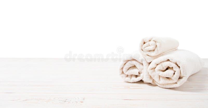 Toalhas brancas roladas na tabela de madeira branca isolada no fundo branco Copie o espa?o e a vista superior Objetos do banheiro fotos de stock