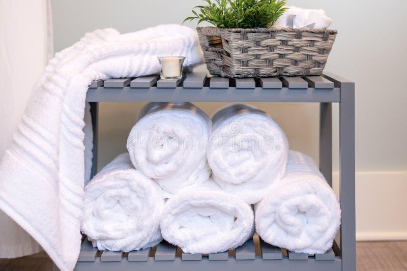 Toalhas de banho brancas macias roladas e empilhadas foto de stock