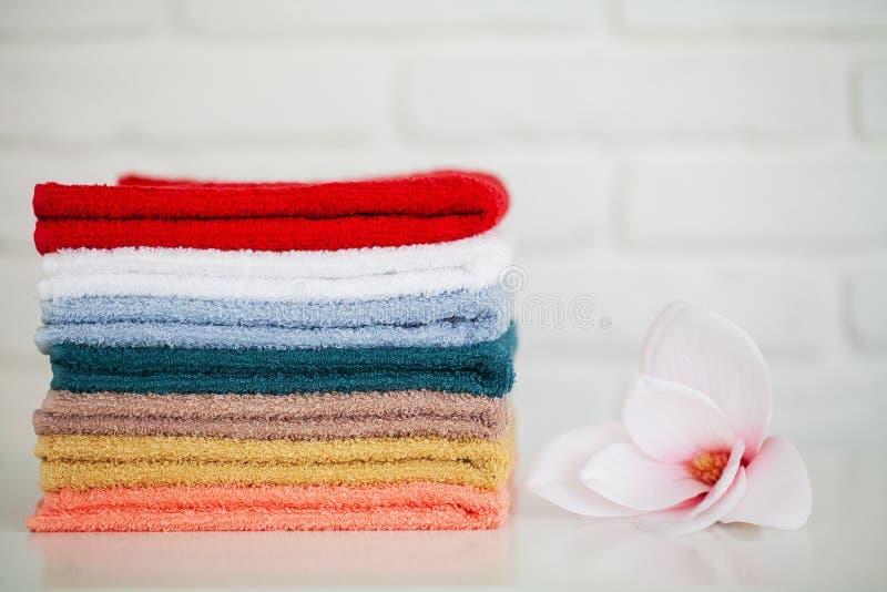 Toalhas de banho macias na tabela de madeira clara com decoração e fundo branco foto de stock royalty free