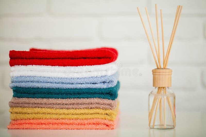 Toalhas de banho macias na tabela de madeira clara com varas do aroma fotos de stock