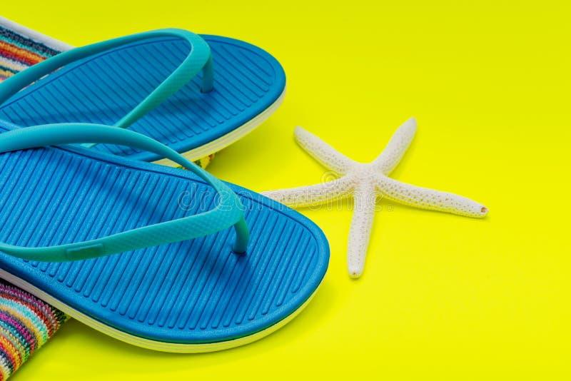 Toalhas de praia orgânicas listradas coloridas dobradas do algodão, Flip Flops azul e estrela do mar do dedo branco no amarelo br imagem de stock