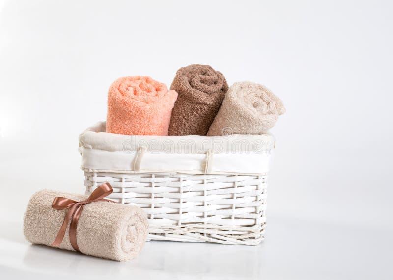Toalhas de terry diferentes roladas com uma fita contra um contexto branco, toalhas das cores em uma cesta branca na frente de um foto de stock