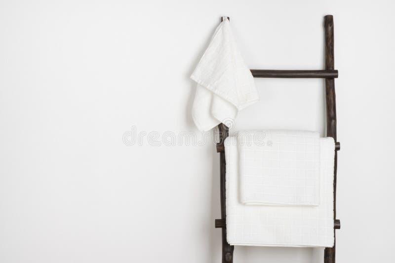 Toalhas dos termas que penduram na escada portátil de madeira do vintage isolada no branco fotografia de stock royalty free