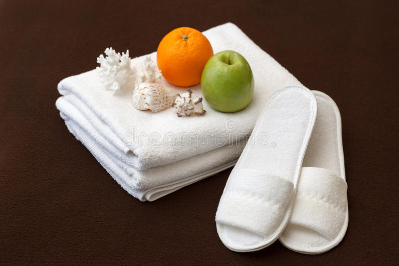 Toalhas e deslizadores brancos na sala de hotel imagem de stock