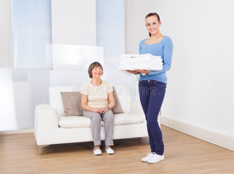 Toalhas levando do guarda com a mulher superior que senta-se no sofá fotos de stock