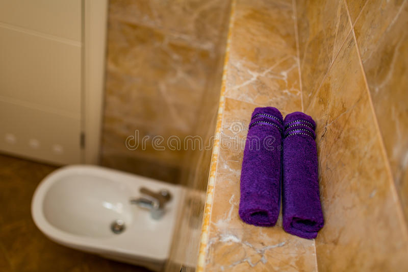 Toalhas roxas no banheiro nos rolos fotografia de stock