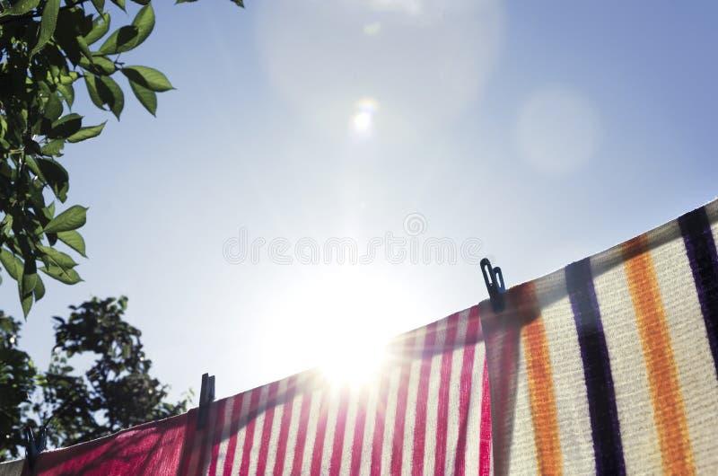 Toalhas secadas na linha de lavagem exterior Luz solar na manh? fotografia de stock royalty free