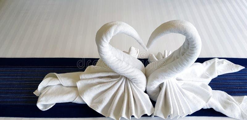 Toalla blanca hermosa doblada en forma del corazón o de dos cisnes en cama en el dormitorio del hotel fotos de archivo