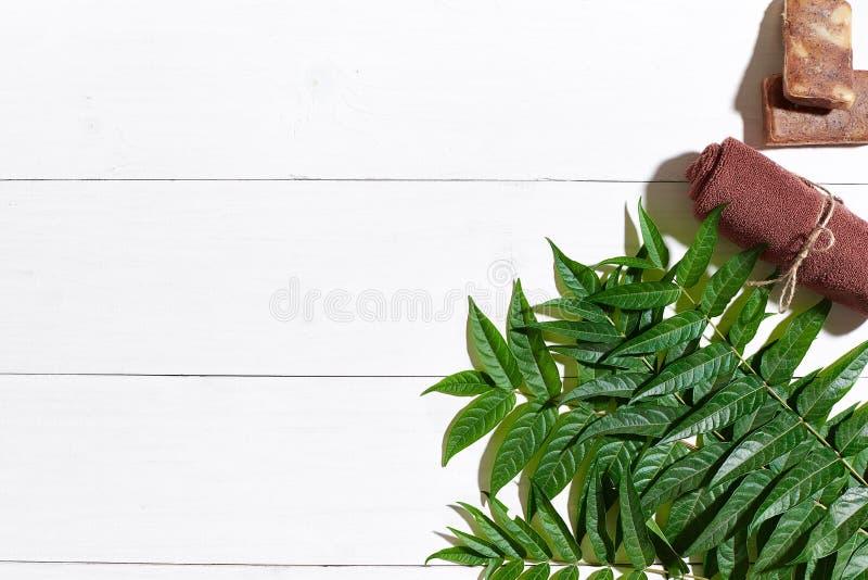 Toalla de Brown y jabón natural del café en la tabla de madera blanca, visión superior foto de archivo libre de regalías
