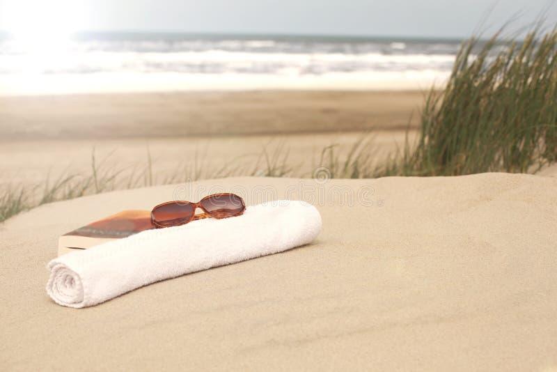 Toalla de las gafas de sol del libro en una playa fotos de archivo