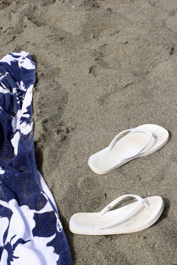 Toalla de playa con los deslizadores foto de archivo libre de regalías