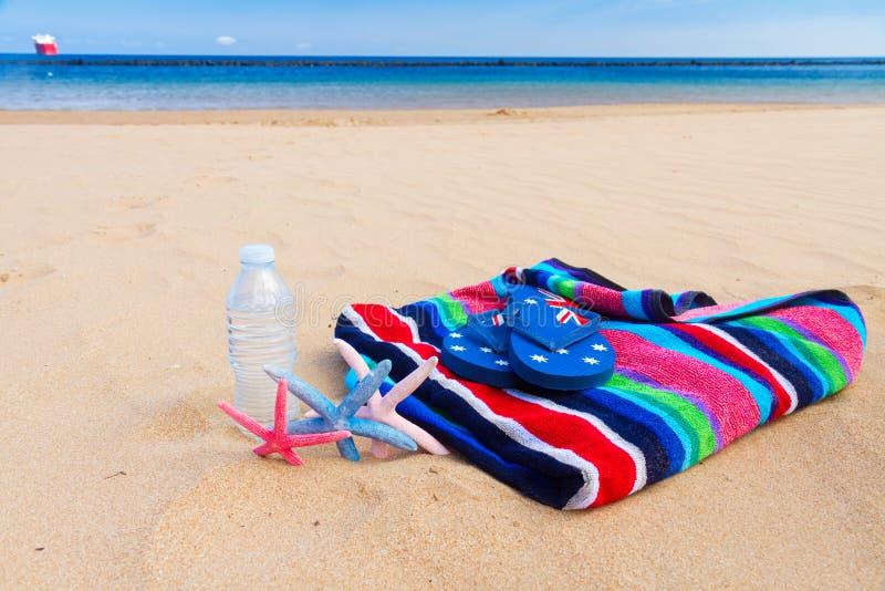 Toalla de playa y botella de agua en la playa arenosa imagen de archivo