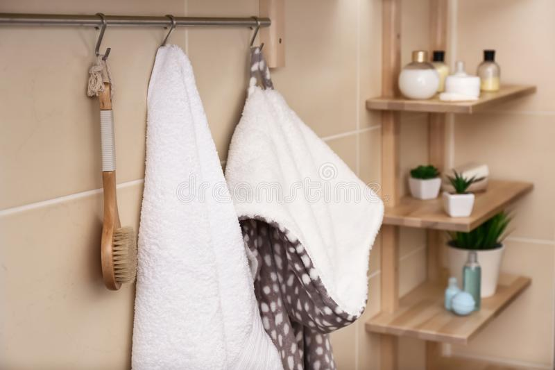 Toalla de Terry, cepillo blanco y albornoz colgando en el estante en cuarto de baño imágenes de archivo libres de regalías