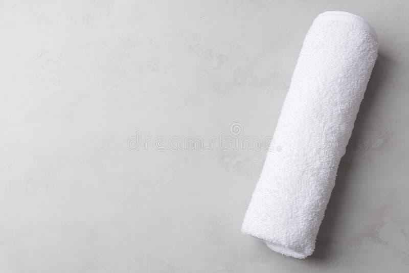 Toalla de Terry mullida blanca limpia rodada en fondo de piedra gris en colores pastel Estilo escandinavo minimalista Higiene del fotos de archivo