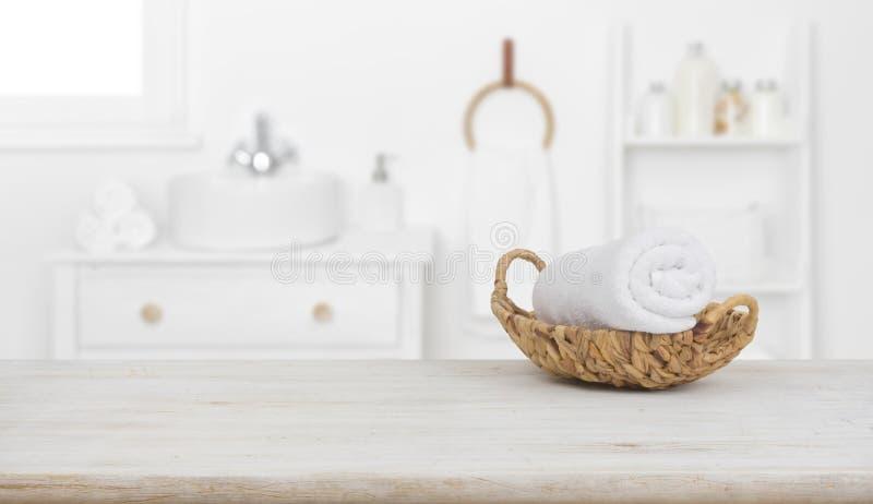 Toalla en una cesta sobre una mesa de madera sobre un fondo de baño borroso imagenes de archivo