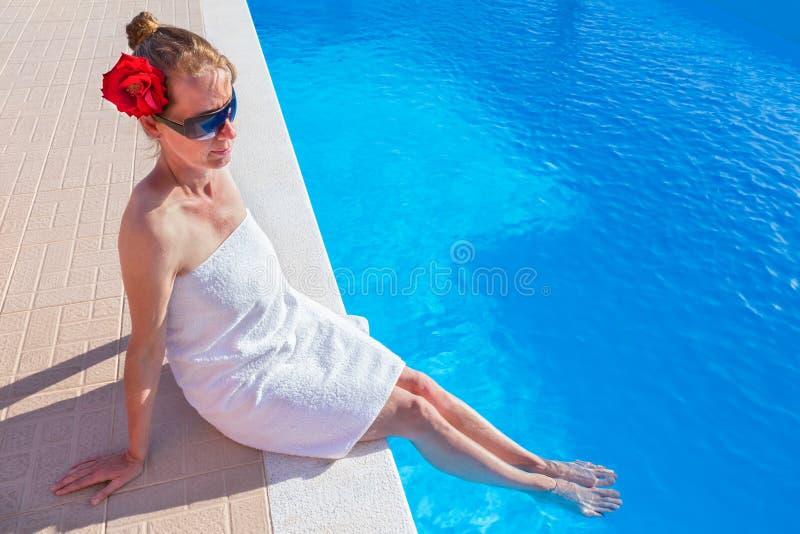 Toalla que lleva de la mujer con los pies en piscina fotografía de archivo