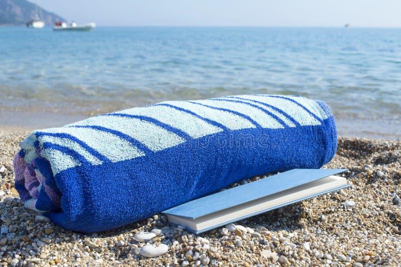 Toalla rodada y un libro en la playa imagen de archivo libre de regalías