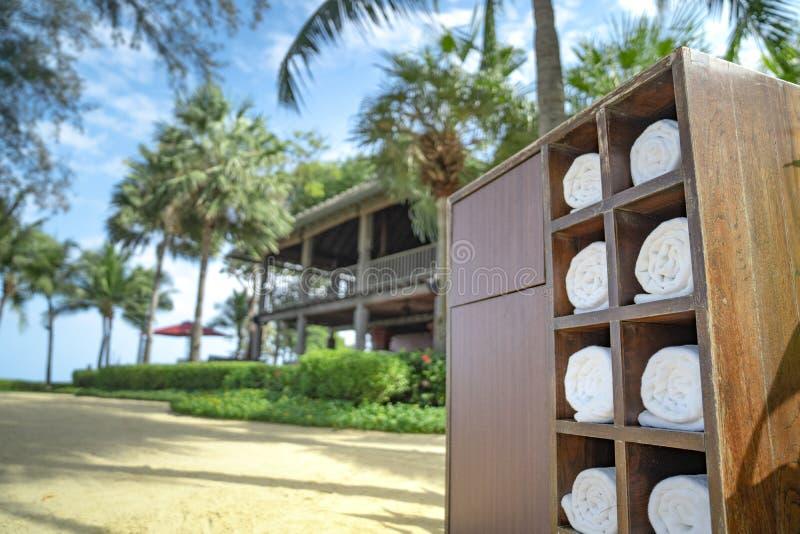 Toalla rodante en la caja cuadrada de madera en el jardín privado de la playa del hotel, preparado para que viajero utilice imagen de archivo libre de regalías