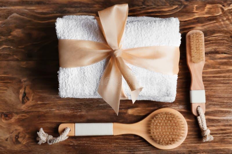 Toalla suave limpia con los cepillos de la cinta y del baño en fondo de madera imagenes de archivo