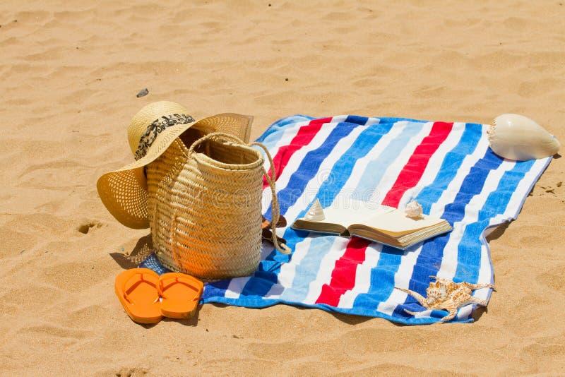 Toalla, tomando el sol los accesorios y el libro fotos de archivo libres de regalías