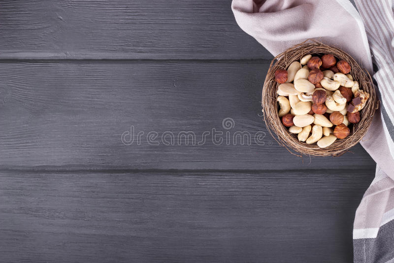 Toalla y cuenco de cocina con las nueces mezcladas en el fondo de madera imagen de archivo