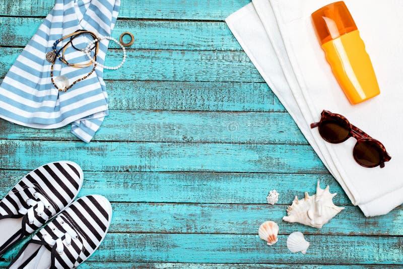 Toalla, zapatos de la playa, gafas de sol, crema del sol en la tabla fotografía de archivo libre de regalías