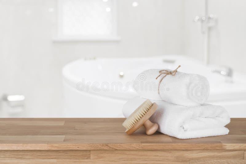Toallas blancas del balneario en la tabla de madera sobre fondo defocused del cuarto de baño imagenes de archivo