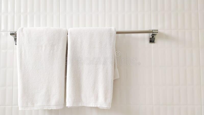 Toallas blancas en el carril del hierro en el cuarto, paredes blancas El dise?o en el cuarto parece hermoso imagen de archivo libre de regalías