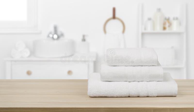 Toallas blancas en la mesa y espacio para copiar sobre el fondo del cuarto de baño fotos de archivo