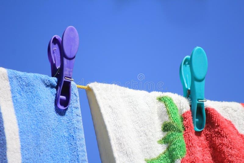 Toallas coloreadas brillantes fijadas a una línea que se lava contra un cielo azul claro foto de archivo