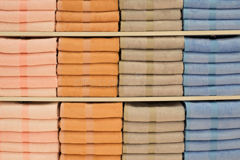 Toallas coloridas con la cesta de mimbre en el estante del fondo del estante foto de archivo