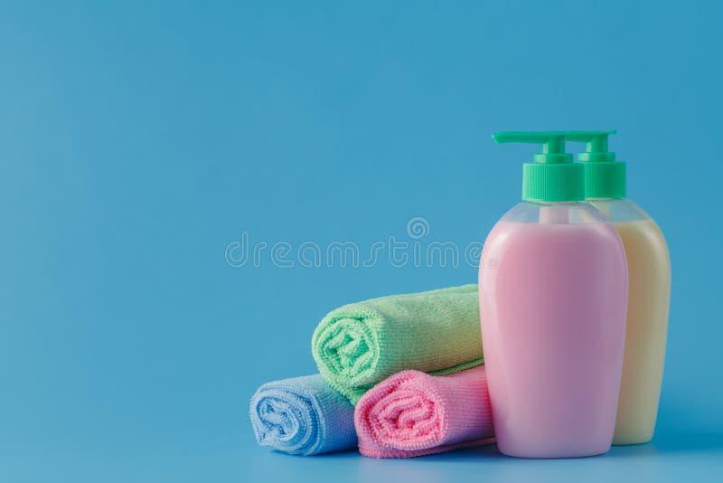 Toallas coloridas y jabón líquido sobre fondo azul fotos de archivo libres de regalías