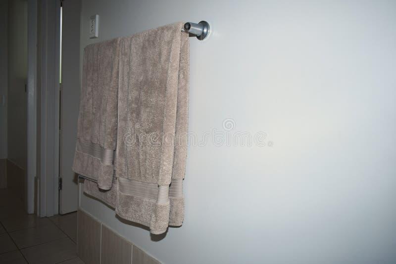 Toallas cubiertas sobre un carril de toalla del acerocromo en una pared imágenes de archivo libres de regalías