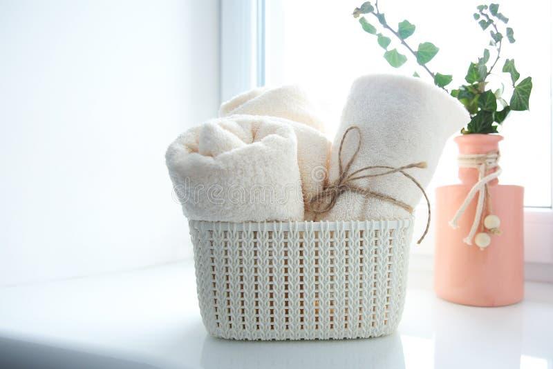 Toallas de baño en cesta en espacio vacío de la copia del travesaño de la ventana foto de archivo libre de regalías