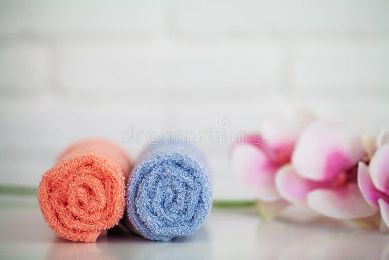 Toallas de baño mullidas con los ingredientes naturales del balneario con las flores de la orquídea fotos de archivo libres de regalías