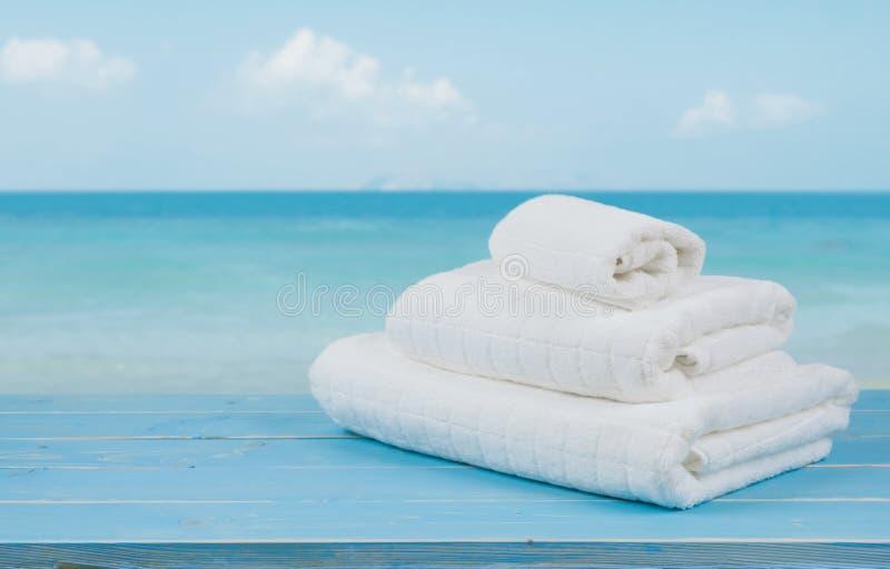 Toallas de playa blancas en la madera sobre fondo azul borroso del mar foto de archivo