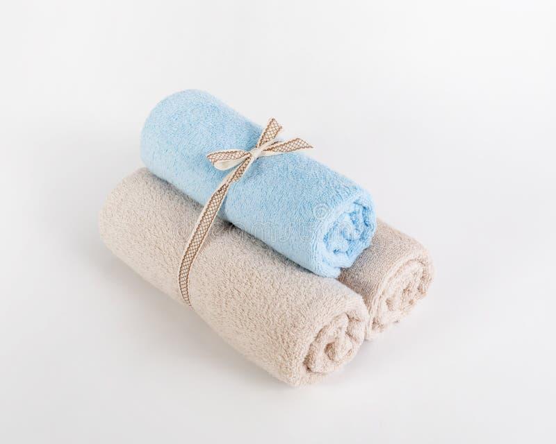 Toallas de Terry azules y beige rodadas en un fondo blanco imagen de archivo
