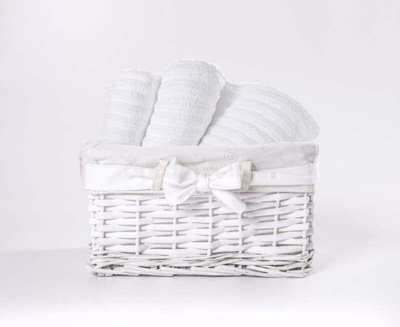 Toallas de Terry suaves blancas rodadas en la cesta contra un contexto blanco Toallas rayadas en una cesta blanca delante de un b imágenes de archivo libres de regalías