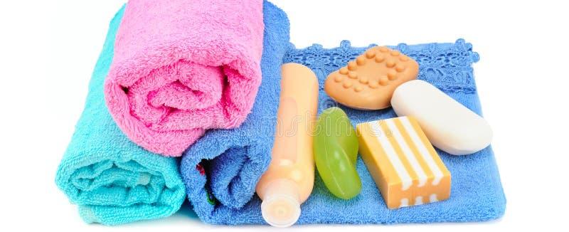 Toallas del algodón, jabón cosmético y champú aislados en blanco wide foto de archivo
